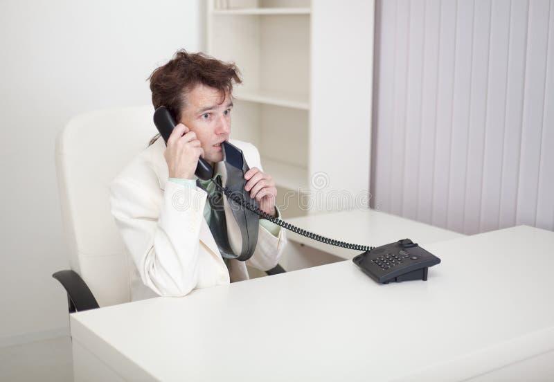 L'uomo d'affari parla sul telefono, preoccupa e mangia il legame immagini stock libere da diritti