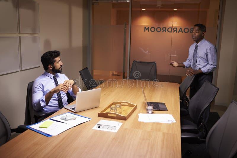 L'uomo d'affari parla tardi con collega in ufficio, vista elevata immagini stock