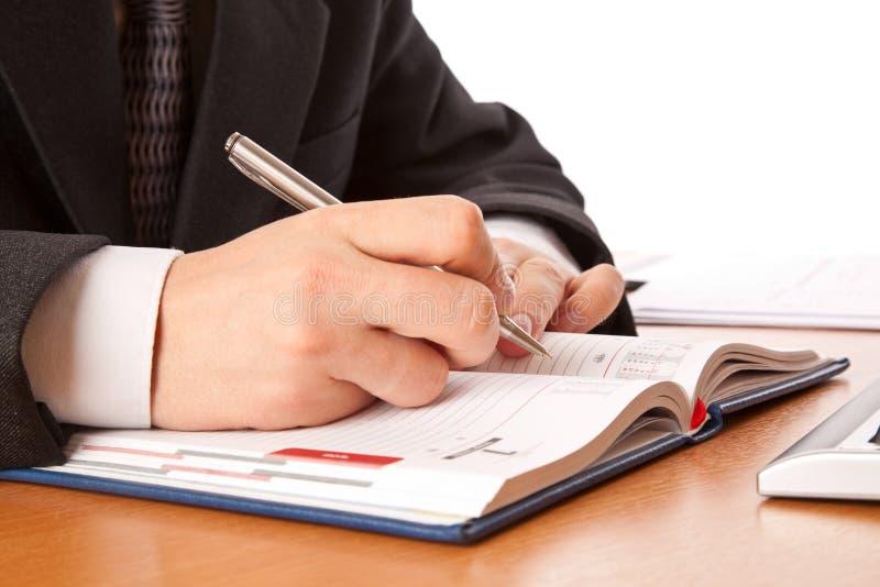 L'uomo d'affari passa la scrittura nell'organizzatore fotografia stock