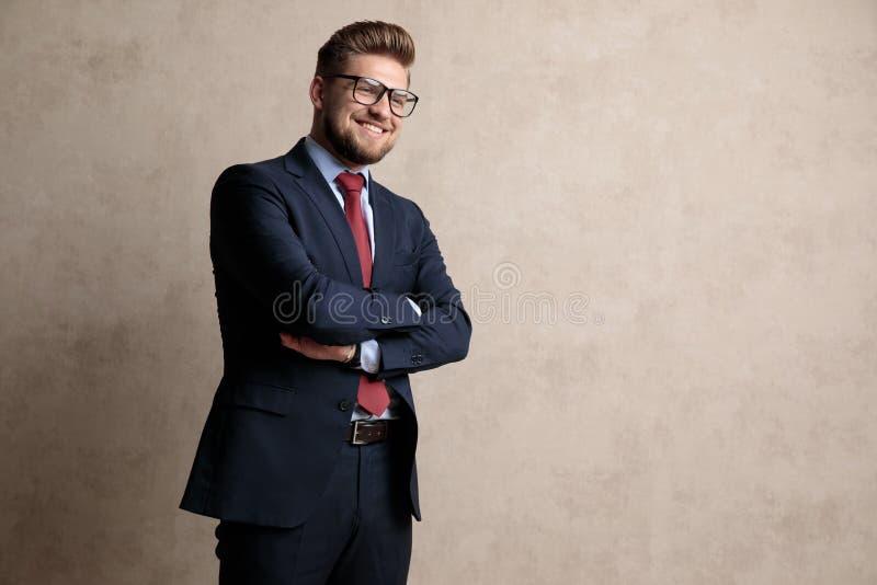 L'uomo d'affari positivo che ride con le sue armi ha attraversato immagini stock