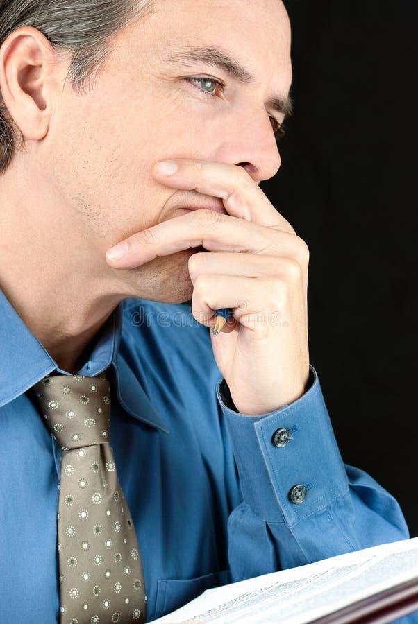 L'uomo d'affari premuroso contempla il documento fotografie stock