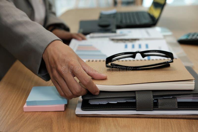 l'uomo d'affari prende il taccuino all'ufficio Uomo che lavora nel luogo di lavoro immagini stock libere da diritti