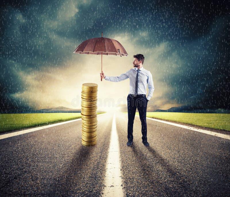 L'uomo d'affari protegge il suo risparmio dei soldi con l'ombrello concetto di assicurazione e di protezione dei soldi fotografie stock libere da diritti