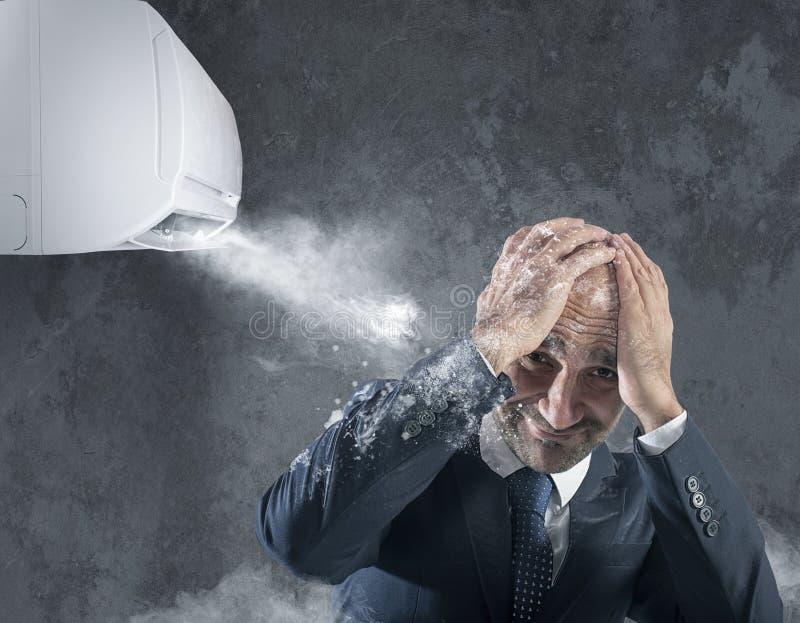 L'uomo d'affari prova a proteggere da se stesso il condizionatore d'aria ghiacciato immagini stock libere da diritti