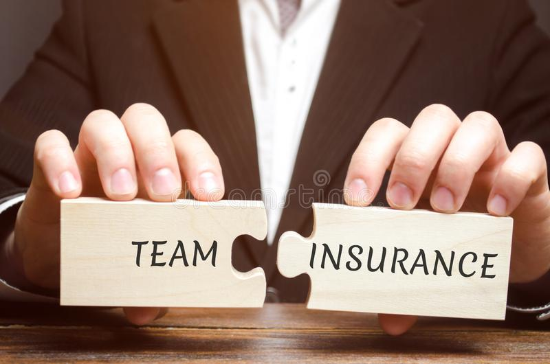 L'uomo d'affari raccoglie i puzzle con le parole Team Insurance Sicurezza e sicurezza in un gruppo di affari Cura per gli impiega fotografie stock