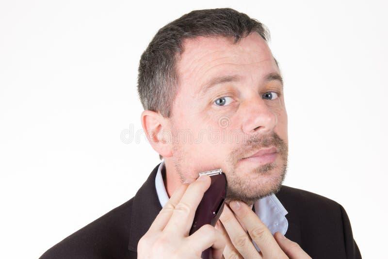 L'uomo d'affari rade la sua barba fuori con un rasoio elettrico fotografie stock