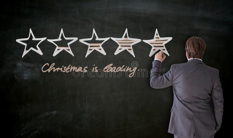 L'uomo d'affari scrive con il Natale del gesso sta caricando il concetto sul bl fotografie stock