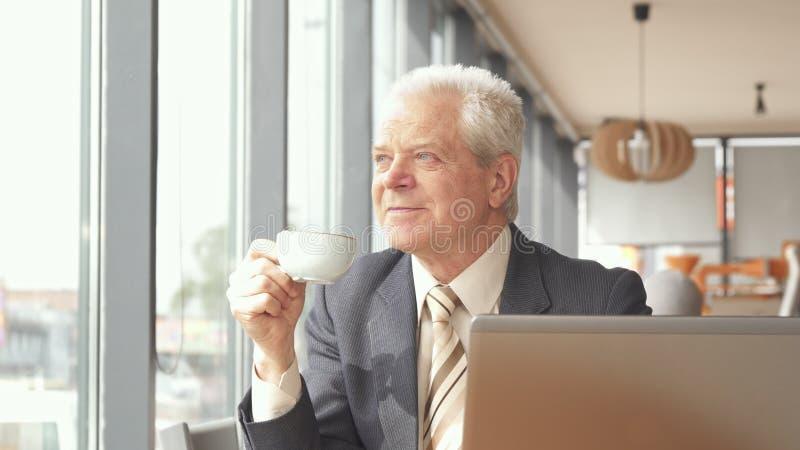 L'uomo d'affari senior esamina fuori la finestra il caffè fotografia stock