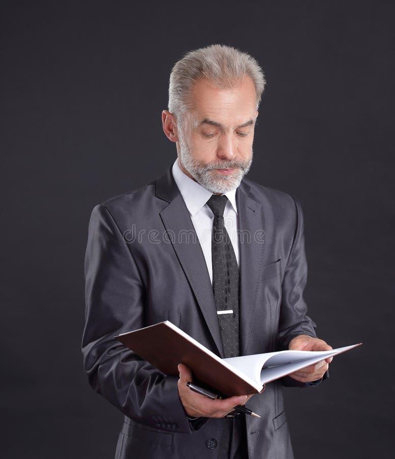 L'uomo d'affari serio firma un documento di lavoro Isolato sul nero fotografia stock