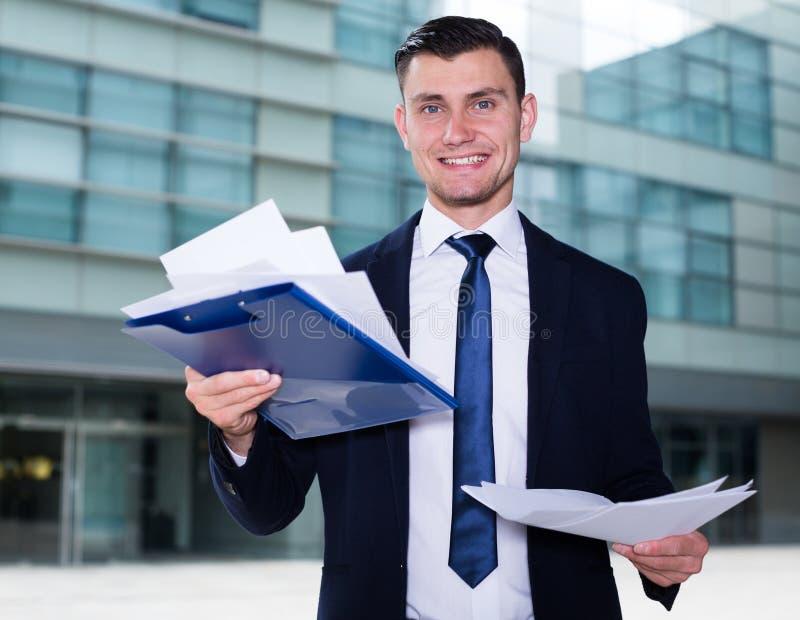 L'uomo d'affari serio sta esaminando i documenti prima della firma immagine stock libera da diritti