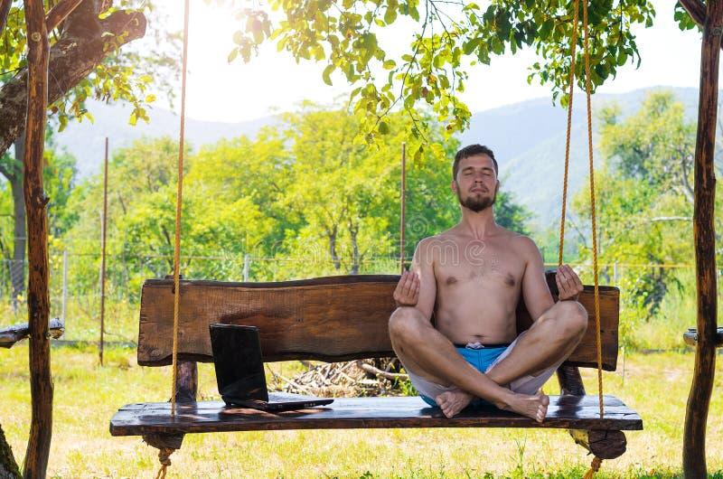 L'uomo d'affari si rilassa dopo avere lavorato al computer portatile che si siede nella posizione del loto fotografie stock libere da diritti