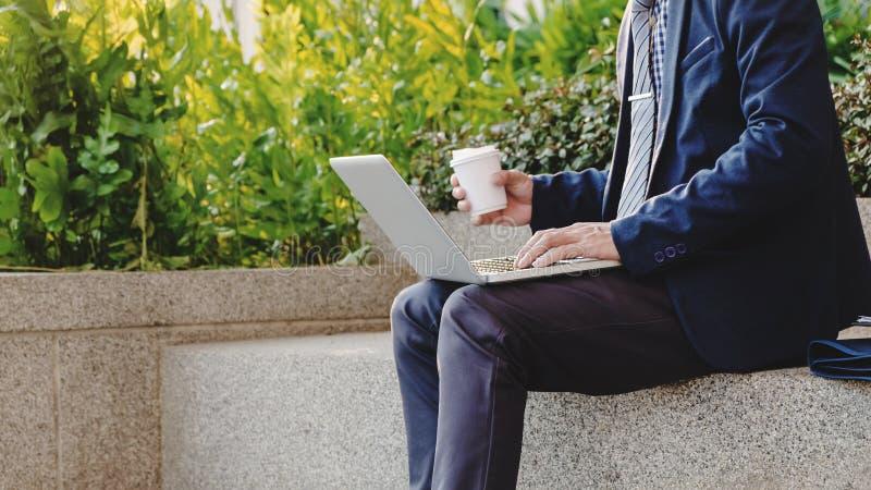 L'uomo d'affari si siede e lavorando al computer portatile circa la risorsa di dati all'aperto con caffè immagine stock