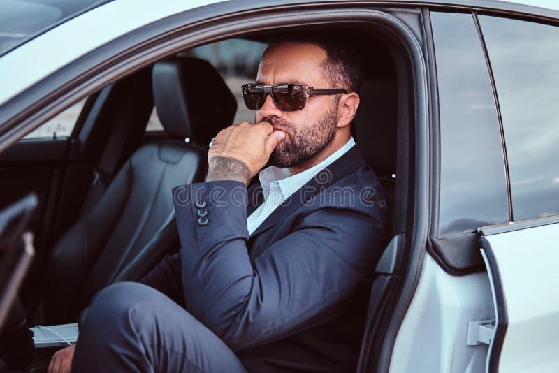 L'uomo d'affari sicuro in occhiali da sole si è vestito in un vestito convenzionale che si siede sui sedili anteriori nell'automo fotografia stock