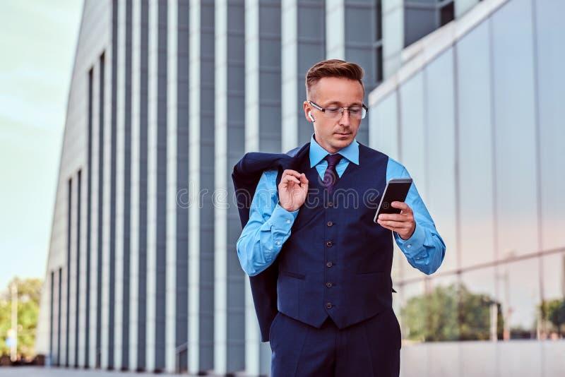 L'uomo d'affari sicuro si è vestito in vestito elegante facendo uso di uno smartphone e tiene il rivestimento sulla spalla mentre immagine stock libera da diritti