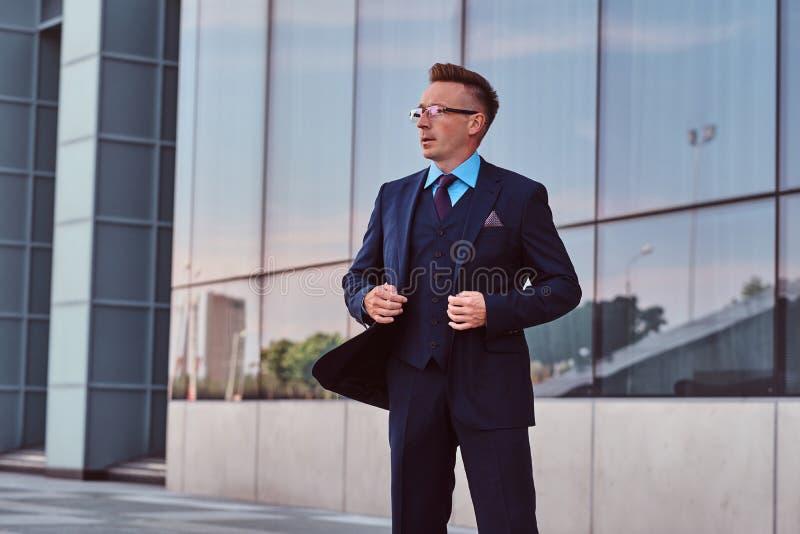 L'uomo d'affari sicuro vestito in un vestito elegante che distoglie lo sguardo e abbottona il suo rivestimento mentre sta all'ape immagini stock