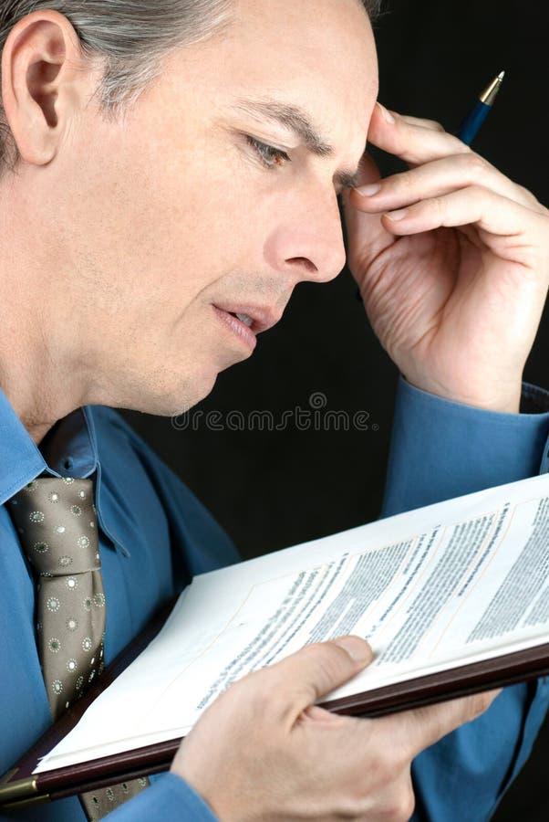 L'uomo d'affari sollecitato legge il documento fotografie stock libere da diritti