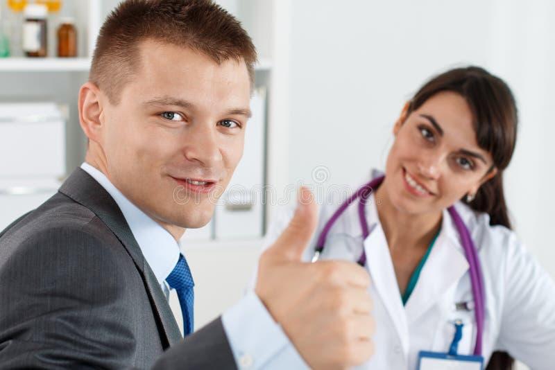 L'uomo d'affari sorridente in vestito che mostra OKAY o l'approvazione firma immagini stock