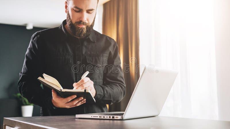 L'uomo d'affari sta facendo una pausa il computer, facente le note in taccuino Sorveglianza dell'uomo webinar, imparando Aducatio fotografie stock