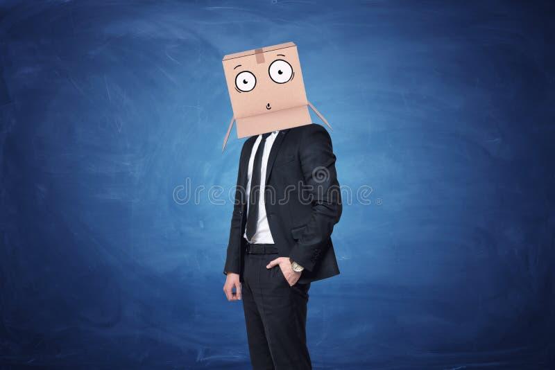 L'uomo d'affari sta indossando la scatola di cartone sulla sua testa con un fronte sorpreso tirato fotografia stock libera da diritti