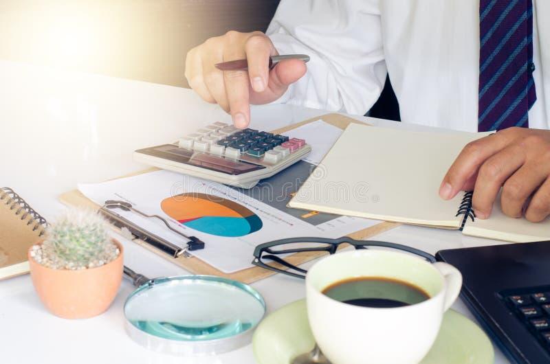 L'uomo d'affari sta lavorando ad una tavola con un dispositivo funzionale è disposto fotografia stock libera da diritti