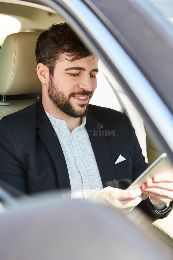 L'uomo d'affari sta leggendo il messaggio sulla compressa fotografie stock