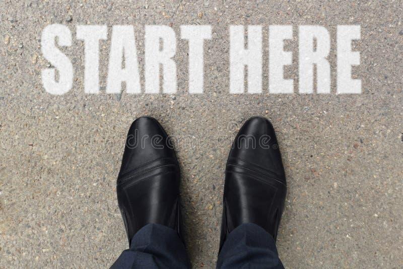 L'uomo d'affari sta osservando giù i suoi piedi su un pavimento di calcestruzzo con le lettere di INIZIO QUI dipinte sulla superf immagine stock