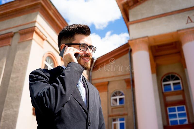 L'uomo d'affari sta parlando sul telefono immagine stock