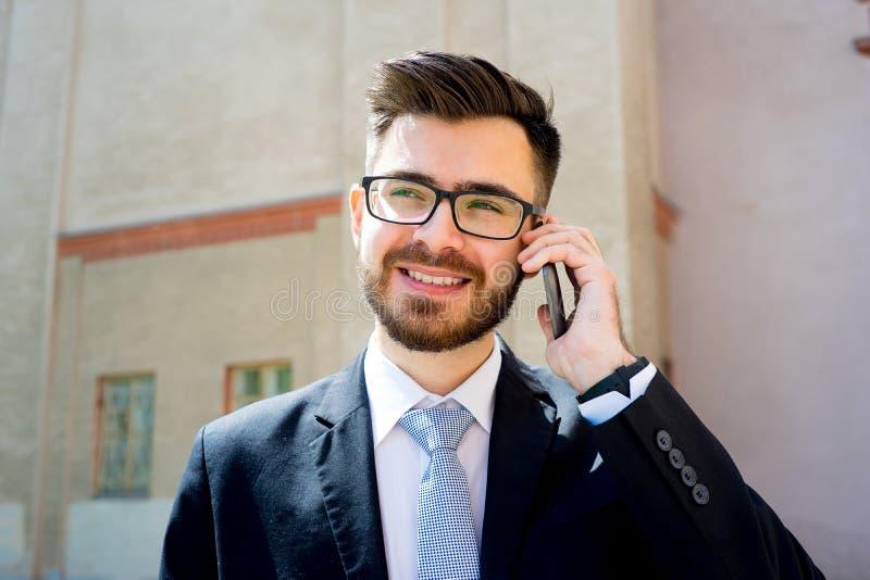 L'uomo d'affari sta parlando sul telefono immagini stock