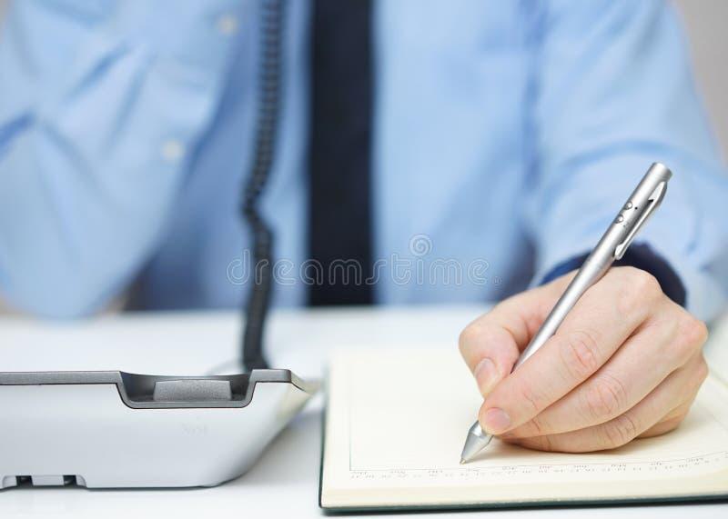 L'uomo d'affari sta parlando sul telefono e sta scrivendo l'appunto fotografia stock libera da diritti