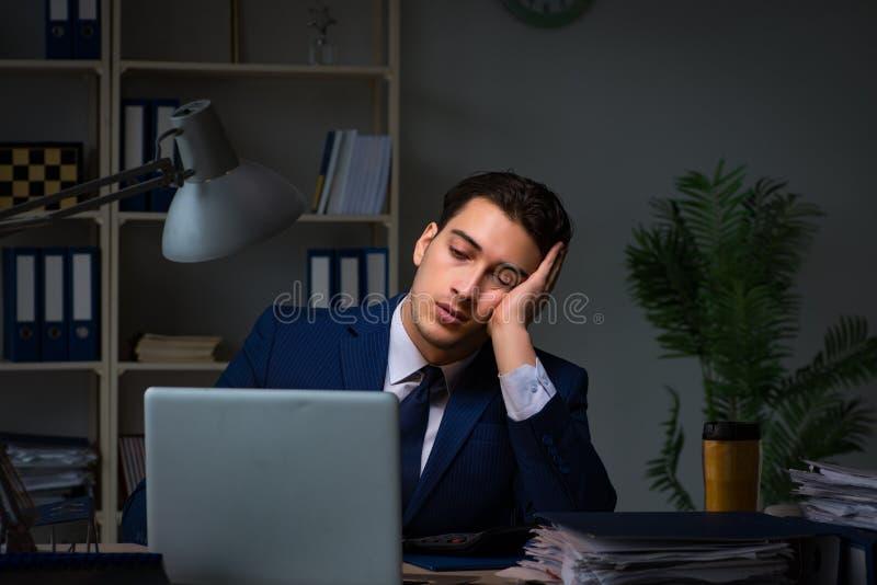 L'uomo d'affari stanco e che dorme nell'ufficio dopo le ore di lavoro straordinario fotografia stock libera da diritti