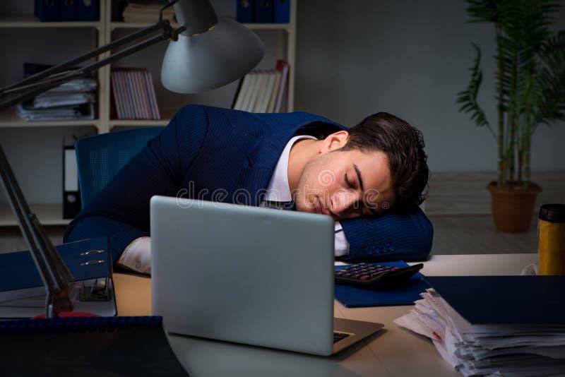 L'uomo d'affari stanco e che dorme nell'ufficio dopo le ore di lavoro straordinario fotografia stock