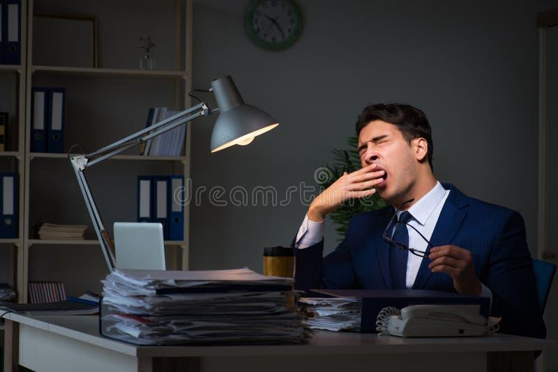 L'uomo d'affari stanco e che dorme nell'ufficio dopo le ore di lavoro straordinario immagine stock libera da diritti