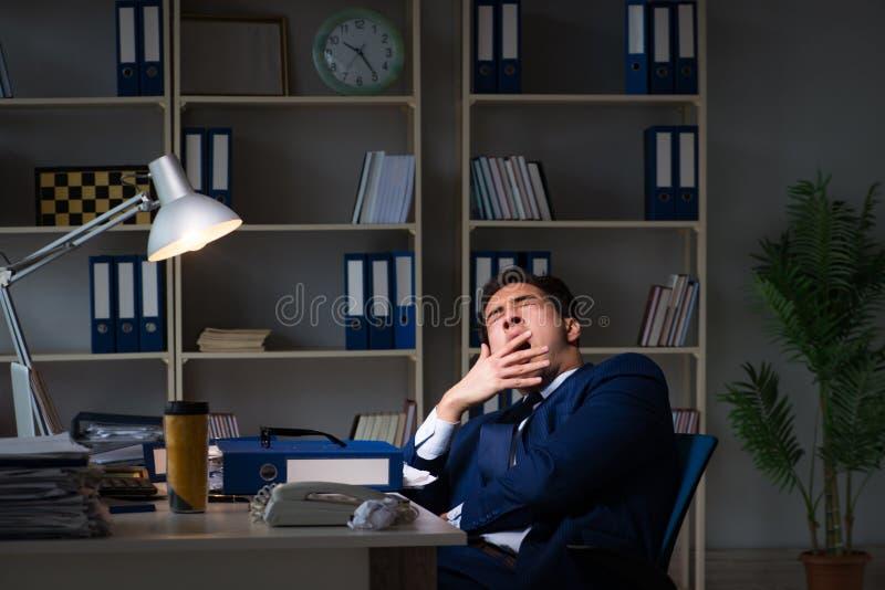 L'uomo d'affari stanco e che dorme nell'ufficio dopo le ore di lavoro straordinario fotografie stock libere da diritti