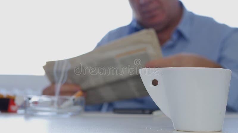 L'uomo d'affari Taking un giornale colto rottura fuma una sigaretta e bere un caffè fotografia stock libera da diritti