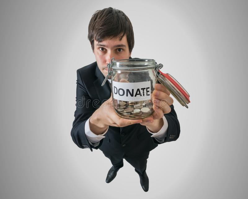 L'uomo d'affari tiene il barattolo con le monete e chiedere la donazione immagini stock