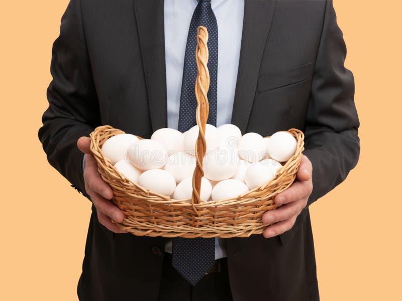 L'uomo d'affari tiene il canestro con le uova fotografia stock
