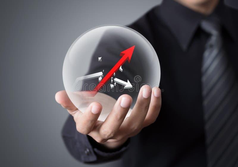 L'uomo d'affari tiene la sfera di cristallo con l'aumento ed il grafico rotto fotografia stock