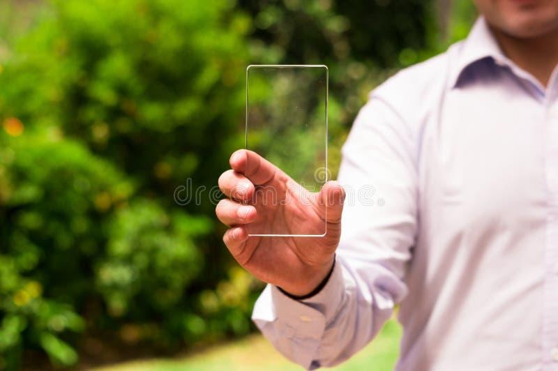 L'uomo d'affari tiene lo Smart Phone trasparente futuristico in sua mano immagini stock libere da diritti