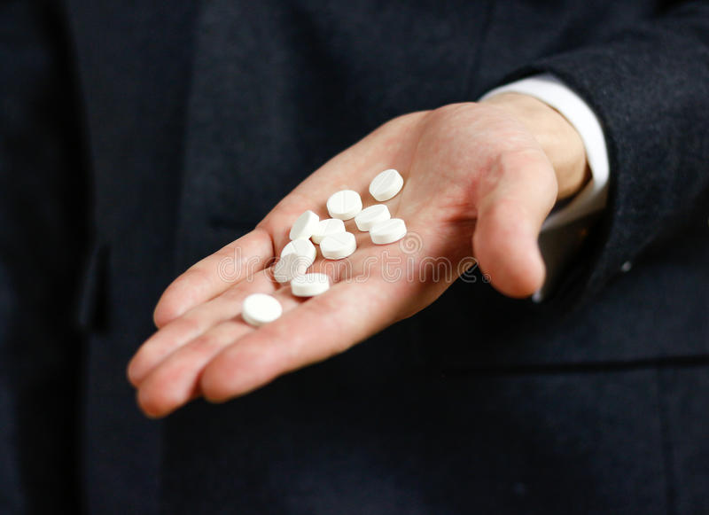 L'uomo d'affari tiene in mani molti pillole e pacchetti bianchi delle compresse immagine stock libera da diritti