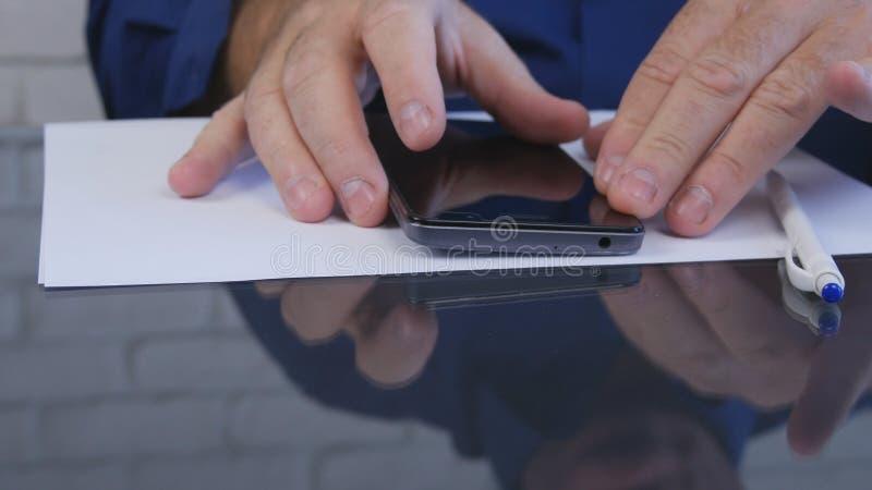 L'uomo d'affari in ufficio ha letto i messaggi ed i email di Smartphone fotografia stock libera da diritti