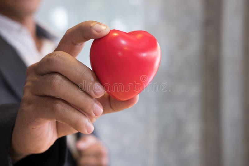 l'uomo d'affari in un vestito mostra il grande cuore rosso al wor dell'ufficio immagine stock libera da diritti