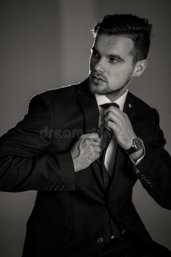 L'uomo d'affari in un vestito nero ed in una camicia bianca sta raddrizzando la h immagine stock libera da diritti
