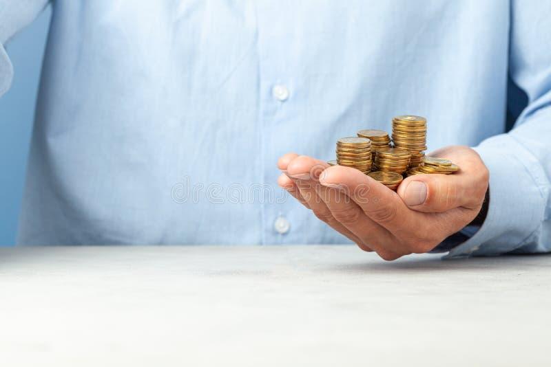 L'uomo d'affari in una camicia blu tiene nel suo lotto della mano delle monete Copi lo spazio per testo fotografia stock libera da diritti