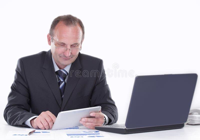 L'uomo d'affari utilizza una compressa digitale mentre si siede al suo scrittorio fotografia stock