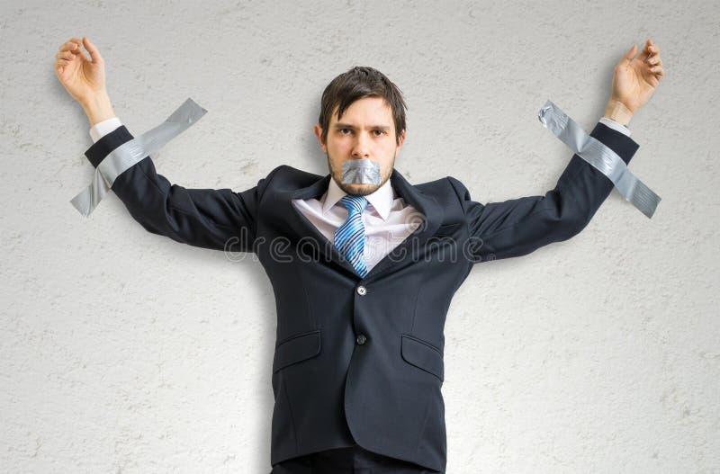 L'uomo d'affari in vestito è legato alla parete con il nastro adesivo fotografia stock