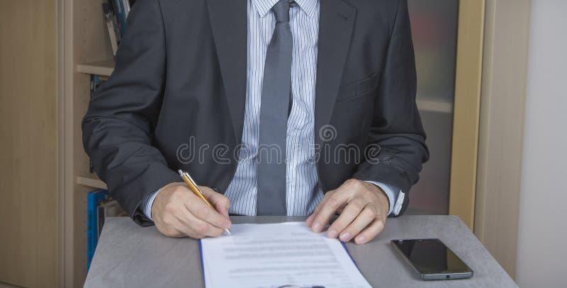L'uomo d'affari in vestito sta firmando un contratto, accordo immagini stock libere da diritti