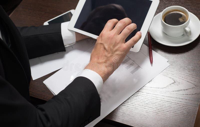 L'uomo d'affari in vestito utilizza la compressa sul caffè della tazza della tavola, cellulare, penna fotografia stock