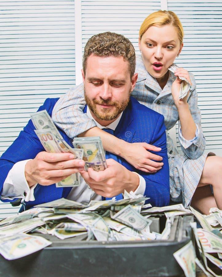 L'uomo d'affari vicino ai dollari dei contanti usufruisce Concetto enorme di profitto girl finanziario tiene un pacchetto di piac fotografie stock libere da diritti