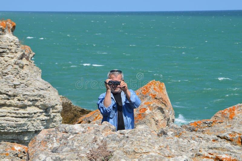L'uomo dai capelli grigio spara il video standind sulle scogliere sopra il verde vede fotografia stock