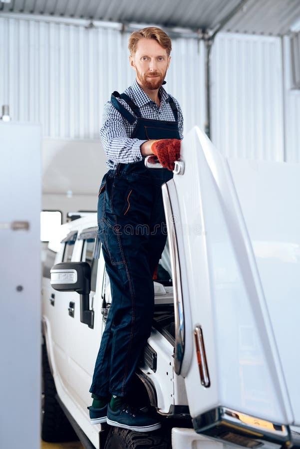 L'uomo dai capelli rossi lavora al servizio automatico Il meccanico è impegnato nella riparazione dell'automobile immagine stock libera da diritti